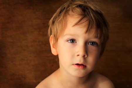blonde hispanic: portrait of a beautiful boy on a brown background