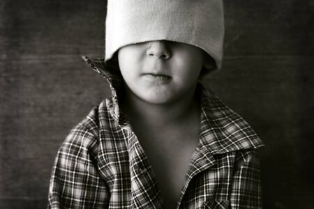portrait of a boy wearing a hat with eyes closed photo