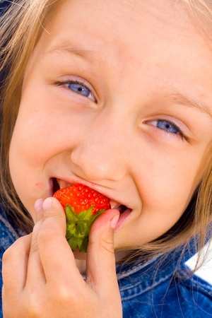 girl in jeans dress eating strawberries photo