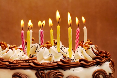 decade: Birthday cake, lit candles on brown background