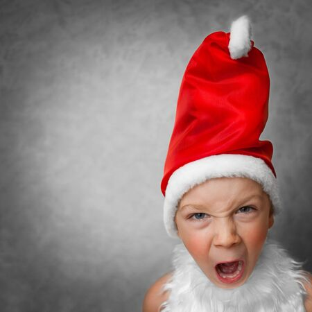 boy in dress Santa Claus shouts photo