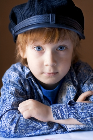 portrait of a handsome boy in a blue shirt and cap photo