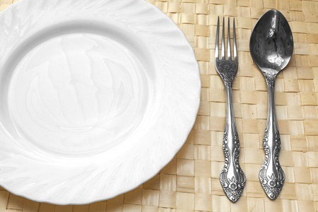 place setting: white plate, spoon and fork on a wicker napkin