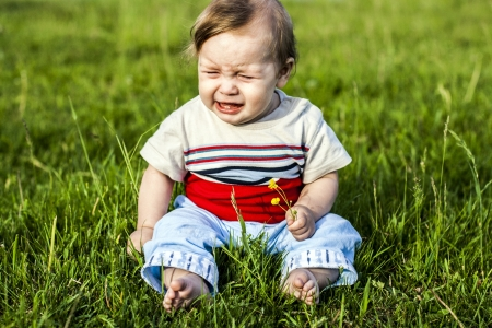 crying boy: little boy sitting on the grass and weeps