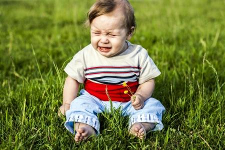 niño llorando: niño sentado en la hierba y llora Foto de archivo