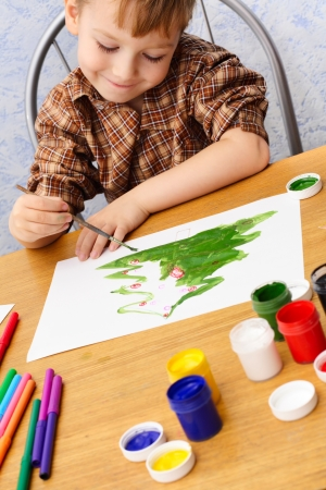 boy paints a Christmas picture photo