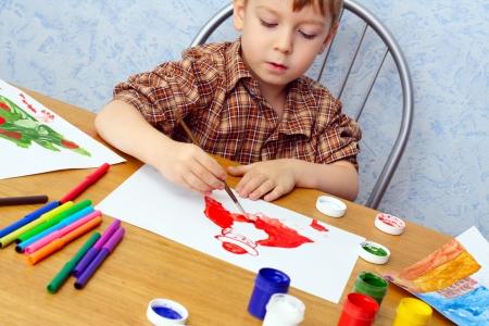 少年がクリスマス絵を描く