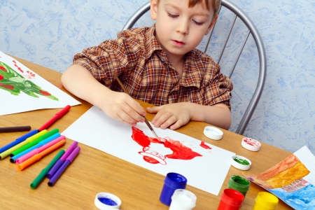 boy paints a Christmas picture
