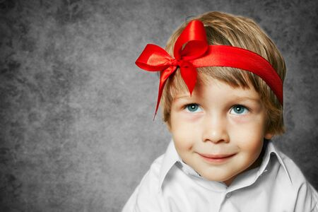 christmas baby: little boy with a red bow in hand Stock Photo