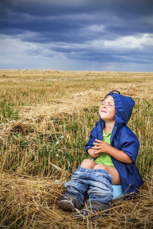 child is sitting in a field on the pot Stock Photo - 15609268