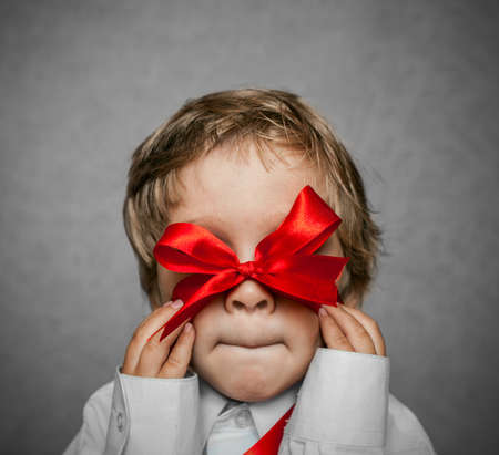 little boy with a red bow in hand photo
