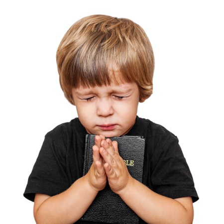 personas orando: Pequeño muchacho rezar con la Biblia en la mano