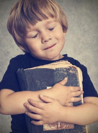 Kleine jongen knuffelen een oud boek, is hij blij Stockfoto