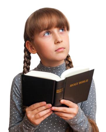 leyendo la biblia: ni�a leyendo un libro en la Biblia y piensa Foto de archivo