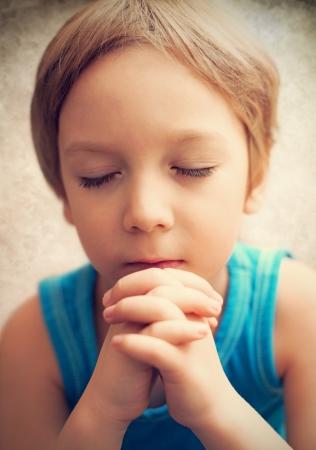 niño orando: un joven que está rezando