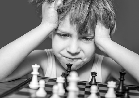 Boy playing chess, thinking how to make a move  photo