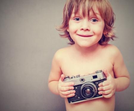 Ragazzino con una vecchia macchina fotografica photo
