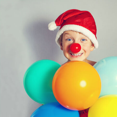 boy in Santa Claus hat holding balloons photo