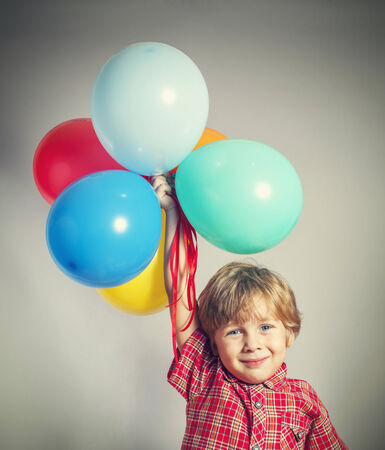 Child holding the bunch of balloons photo