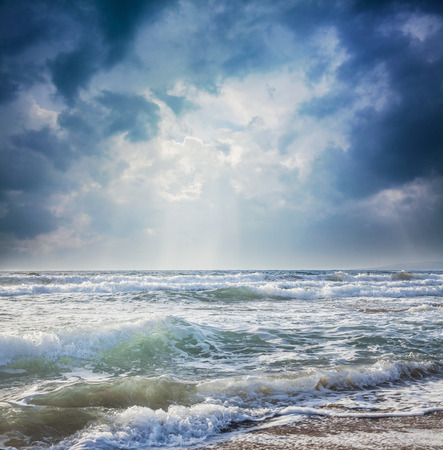 condition: Rays of light from the dark sky on a stormy sea
