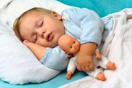 Portret van peuter kind, slapen in een bed met een speelgoed pop