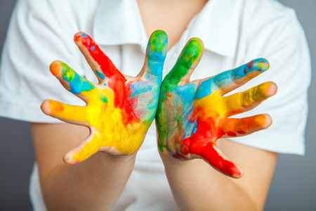 klein meisje en jongen handen geschilderd in kleurrijke verf Stockfoto