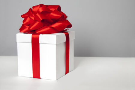 White gift box with red ribbon bow photo