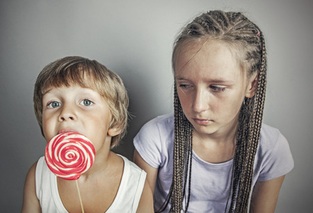 brother sister: sister jealous brother who eats candy Stock Photo