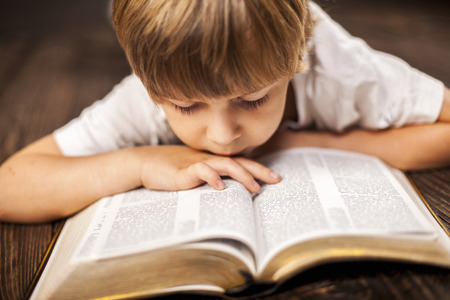 kid reading: little boy studying the scriptures. Stock Photo