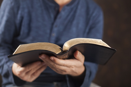 black gods: Man reading from the holy bible, close up Stock Photo