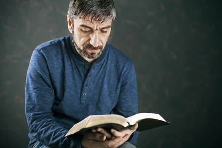 bible light: Man reading from the holy bible, close up Stock Photo
