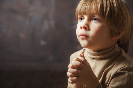 Little young beautiful boy spiritual peaceful praying and wishing
