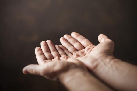 handen bedelen op een bruine achtergrond