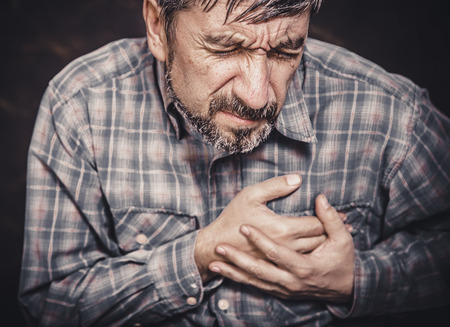 dolor de pecho: Hombre que tiene dolor en el pecho