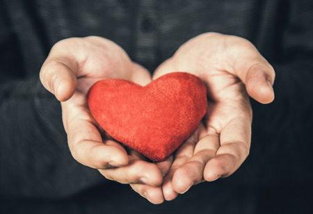 man holding red heart in her hands