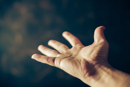 mano de dios: manos pidiendo limosna en un fondo marr�n