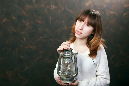 kerosene lamp: Beautiful girl with a kerosene lamp in hands Stock Photo