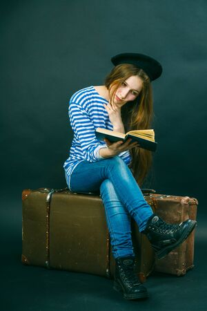 caucasian girl: Caucasian girl reading a book while sitting on a suitcase Stock Photo