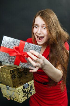Portret van casual jonge tevreden glimlachende vrouw houdt rode geschenk doos. Geïsoleerde studio achtergrond vrouwelijke model.