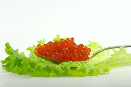 Close-up of silver spoon with caviar on the lettuce leaf