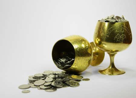 Two golden beakers full of money