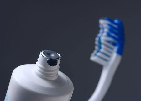 toothcare: close-up of new tooth-paste and brush on dark background