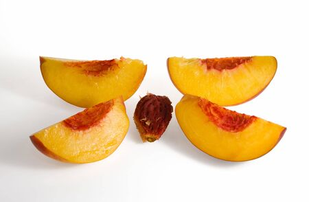 four peach slices and stone on white background