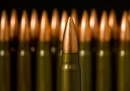 Macro of gun machine bullet over many standing cartridges background photo