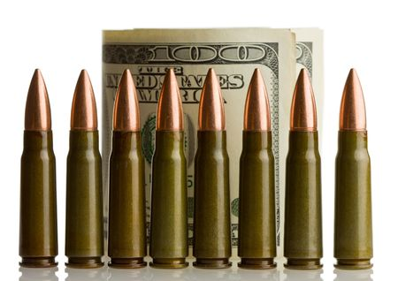 Cartridges arranged in line as fence in front of dollars roll Stock Photo