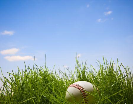 Macro honkbal over blauwe hemel en gras achtergrond - concept van de zomer tijd activiteit  Stockfoto