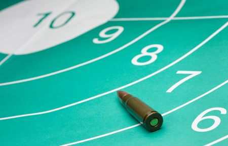 close-up of gun target and cartridge aimed at bullseye photo