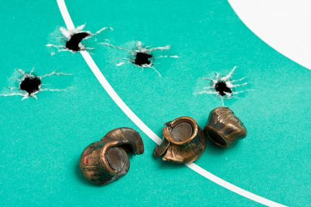 Macro of three squashed bullets on gun target with bullet holes photo