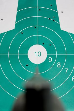 Close up of revolver against body target, shallow DOF, focus on target