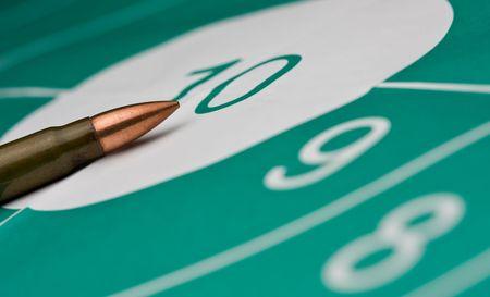 macro van pistool papier doel en kogel, ondiepe DOF, focus op cartridge  Stockfoto